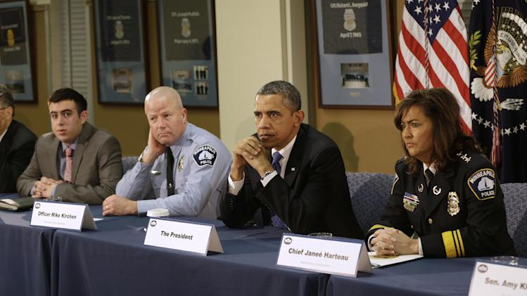President Barack Obama listens with local leaders and law enforcement officials while participating in a roundtable discussion at the Minneapolis Police Department Special Operations, Monday, Feb. 4, 2013, in Minneapolis, Minn. From left are, Samuel Rahamin, Minneapolis Police  Officer Mike Kirchen, the president, Minneapolis Police Chief Janee Harteau.  (AP Photo/Pablo Martinez Monsivais)