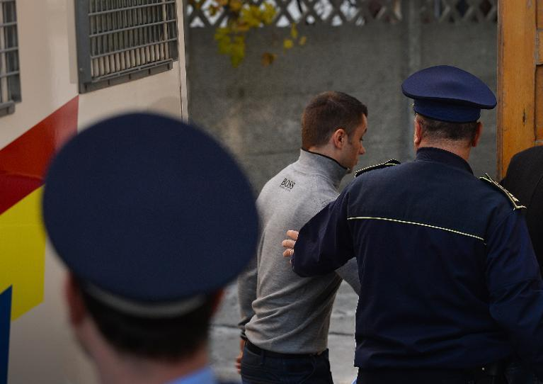 Romanian Radu Dogaru (C), one of six suspects on trial for a heist at the Kunthal museum in Rotterdam, enters a court in Bucharest on October 22, 2013