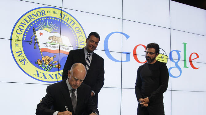 California Gov. Edmund G Brown Jr. signs a bill for driverless cars as state Senator Alex Padilla, center, and Google co-founder Sergey Brin, right, look on at Google headquarters in Mountain View, Calif., Tuesday, Sept. 25, 2012.  The legislation will open the way for driverless cars in the state. Google, which has been developing autonomous car technology and lobbying for the legislation has a fleet of driverless cars that has logged more than 300,000 miles (482,780 kilometers) of self-driving on California roads. (AP Photo/Eric Risberg)