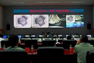 <p>Chinese technicians at the Jiuquan Space Centre monitor the Shenzhou-9 spacecraft as it prepares to link with the Tiangong-1 module. A Chinese spacecraft has successfully completed the country's first manual docking in orbit, a milestone in an ambitious programme to build a space station by the end of the decade.</p>