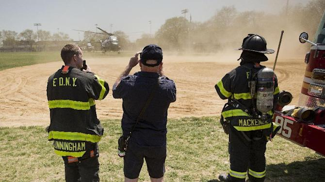 "Members of the New York Fire Dept., watch the landing of Marine One helicopter, with President Barack Obama aboard, at a baseball field at Lehman College in New York, Monday, May 4, 2015. Obama traveled to the college in the Bronx to promote the ""My Brother's Keeper"" program, which works to give young men of color more opportunities through mentoring and business partnerships. (AP Photo/Pablo Martinez Monsivais)"