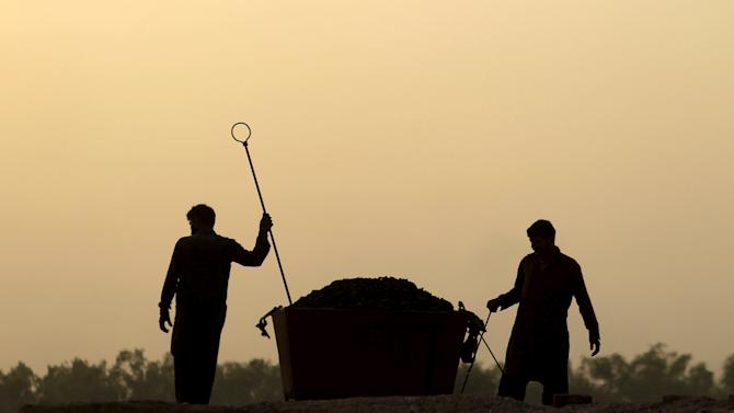 Men work at a brick-making factory on the outskirts of Islamabad