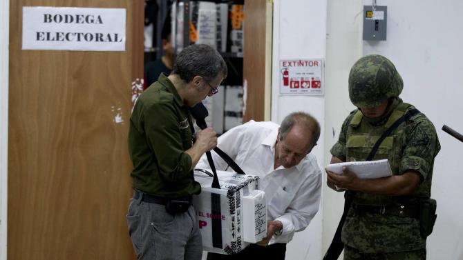 Mexican authorities check a ballot box during a computation of ballot boxes at an electoral institute district council in Mexico City, Wednesday July 4, 2012. The computation is done to determine which ballot boxes used in last Sunday's general elections will be recounted in front of party representatives. (AP Photo/Eduardo Verdugo)