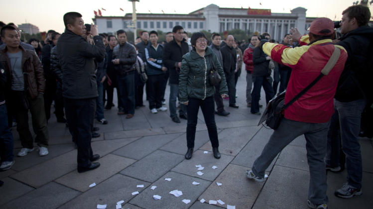 A woman, center, yells after she threw protest papers on Tiananmen Square after a flag raising ceremony while a plainclothes security person, in red, stops a journalist, right, from taking videos, near the Great Hall of the People, where the 18th Communist Party Congress will be held later in the morning, in Beijing, China, Thursday Nov. 8, 2012. (AP Photo/Alexander F. Yuan)