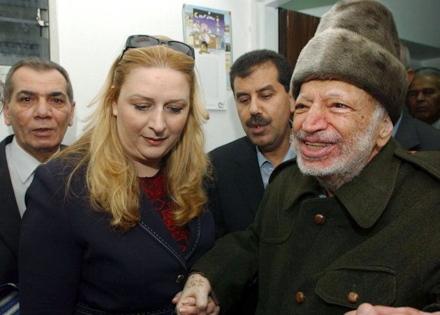 In this Friday, Oct. 29, 2004 file photo, Palestinian leader Yasser Arafat and his wife Suha hold hands prior to Arafat's departure from his compound in the West Bank town of Ramallah in this file picture released by the Palestinian Authority. asser Arafat's body may be exhumed to allow for more testing of the causes of his death, the Palestinian president said Wednesday, July 4, 2012, after a Swiss lab said it found elevated levels of a radioactive isotope in belongings the Palestinian leader is said to have used in his final days.