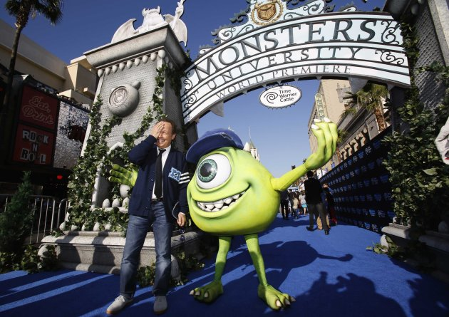 "Cast member Billy Crystal poses with a life-size character of Mike, whom he voices in the movie, at the premiere of the film ""Monsters University"" at El Capitan theatre in Hollywood"