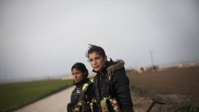Kurdish female members of the Popular Protection Units stand guard at a check point near the northeastern city of Qamishli, Syria, Sunday, March 3, 2013. (AP Photo/Manu Brabo)