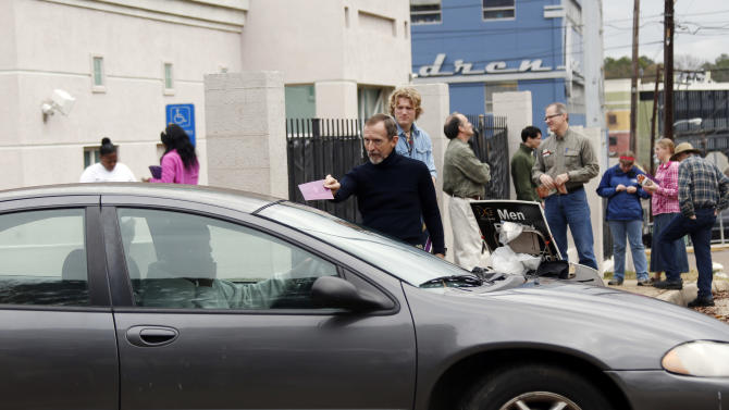 FILE - In this Friday, Jan. 11, 2013 file photo, an anti-abortion demonstrator attempts to give a leaflet to a driver leaving the Jackson Women's Health Organization Inc., Mississippi's only commercial abortion clinic in Jackson, Miss., while other abortion foes gather to pray. The organization's administrator, Diane Derzis, says the three principal physicians on her staff have been unable to get admitting privileges at area hospitals due to pressure from the anti-abortion movement. (AP Photo/Rogelio V. Solis, File)