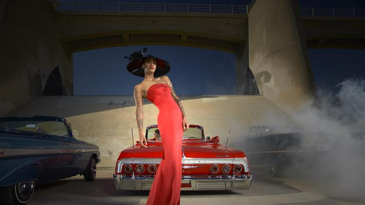 "Azmarie models a British couture hat while posing with a vintage American car on ""America's Next Top Model."""