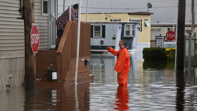 A member of the Moonachie Department of Public Works talks to a resident at the Metropolitan Trailer Park in Moonachie, N.J., Tuesday, Oct. 30, 2012. The park was flooded in the wake of superstorm Sandy. (AP Photo/Craig Ruttle)