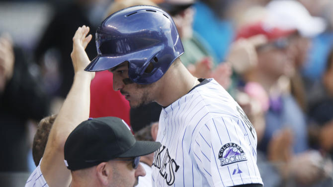 Colorado Rockies' Nolan Arenado, right, heads back to dugout after exchanging words with San Francisco Giants catcher Buster Posey while crossing home plate after hitting a three-run home run in the fourth inning of a baseball game Sunday, May 24, 2015, in Denver. (AP Photo/David Zalubowski)