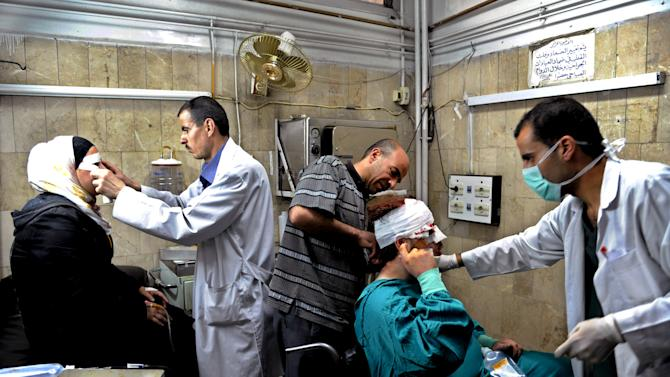 In this photo released by the Syrian official news agency SANA, Syrian doctors treat citizens who were injured in an  explosion, in the central district of Marjeh, Damascus, Syria, Tuesday April 30, 2013. A powerful explosion rocked Damascus on Tuesday, causing scores of casualties, a day after the country's prime minister narrowly escaped an assassination attempt in the heart of the heavily protected capital. (AP Photo/SANA)