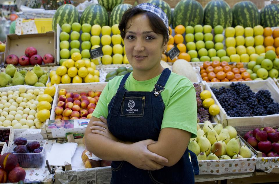 In this Aug. 22, 2012, photo, Uzbekistan native Anora, 27, poses for a photo at her market stand where she sells fruit in Moscow. The old Moscow is rapidly giving way to a multi-ethnic city where Muslims from Central Asia are the fastest growing sector of the population. (AP Photo/Misha Japaridze)