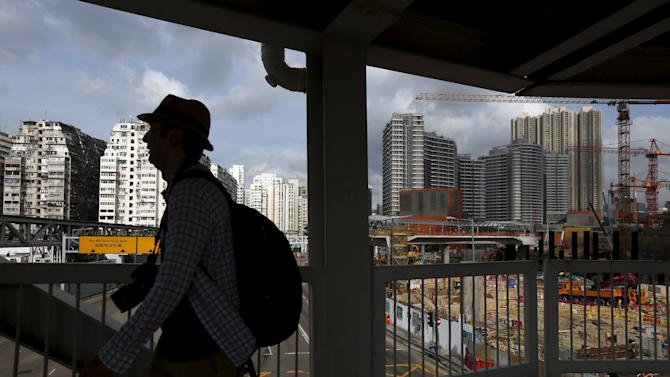 Man walks on a footbridge as 45-year-old residential flats, the latest luxury homes and a construction site are seen in the background, in West Kowloon, Hong Kong, China