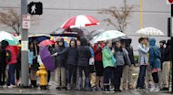 School children huddle under umbrellas as they wait to cross a street during an outing Monday, Nov. 19, 2012, in Seattle. Wet and windy weather with mountain snow will continue this week in Washington, but there may be a lull for turkeys to land on Thanksgiving Day tables, forecasters said. More Pacific storms that started rolling across the Northwest in waves over the weekend are on their way, according to the National Weather Service. (AP Photo/Elaine Thompson)