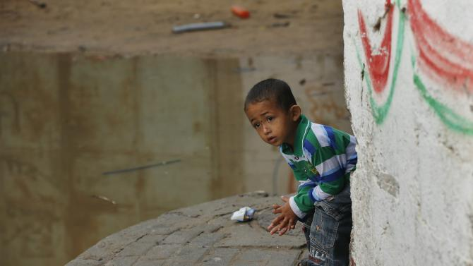 A Palestinian boy looks at a street flooded with sewage water from a sewage treatment facility in Gaza City