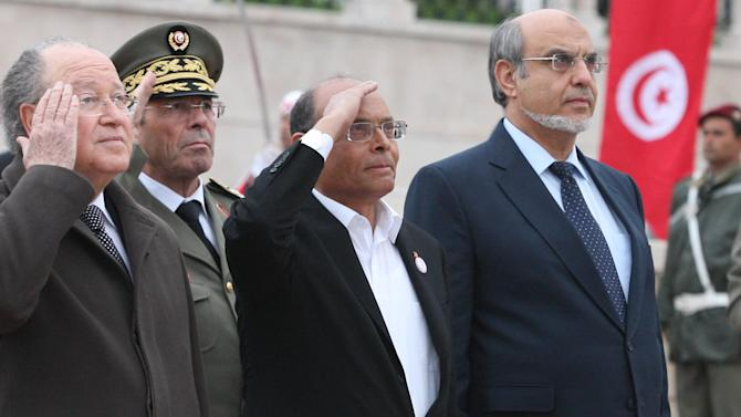 Tunisian Presidnet Moncef Marzouki, center, head of governement Hamadi Jebali, right, and head of constitutional assembly the Mustapha Ben Jaafar, left.  salute the national flag during a ceremony marking the second anniversary of the Revolution, Monday, Jan. 14. 2013 in Tunis. Two years after the revolution that overthrew an authoritarian president and started the Arab Spring, Tunisia is struggling with high unemployment and rising violence in its politics. (AP Photo/Amine Landoulsi)