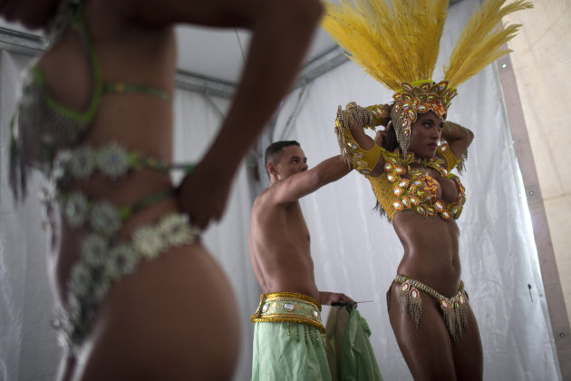 In this photo taken Saturday, Feb. 2, 2013, samba dancer Diana Prado, right, is with her costume as she prepares for a carnival parade at central station in Rio de Janeiro, Brazil. Though samba dancers, or &quot;passistas,&quot; as they&#39;re known in Portuguese, are unquestionably the star attractions of the world&#39;s most iconic Carnival celebrations, they&#39;re not on the payroll of the samba school they represent. (AP Photo/Felipe Dana)
