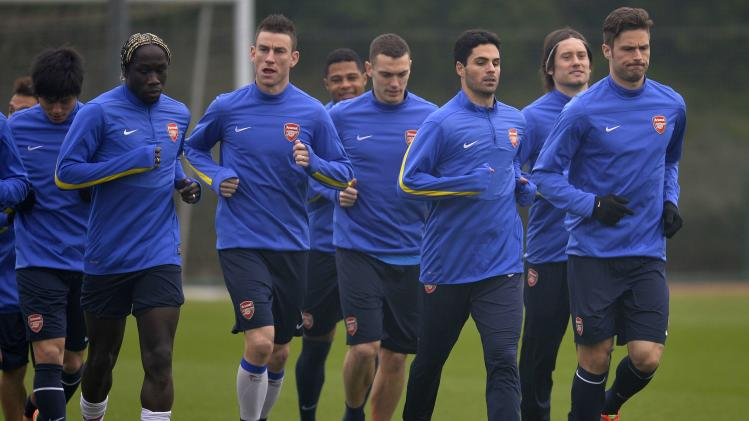 Arsenal team members led by Olivier Giroud (R) warm up during a training session at London Colney near London