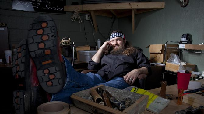 "This undated photo provided by A&E, shows Willie Robertson, star of A&E's ""Duck Dynasty,"" at his desk in his office at the Duck Commander warehouse in West Monroe, La. Turning small business owners into stars has become a winning formula for television producers, but some businesses featured in them are cashing in, too. Sales explode after just a few episodes air, transforming these nearly unknown small businesses into household names. In addition to earning a salary from starring in the shows, some small business owners are benefiting financially from opening gift shops that sell souvenirs or getting involved in other ventures that spawn from their new-found fame. (AP Photo/A&E)"