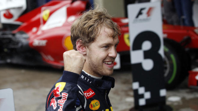 Red Bull driver Sebastian Vettel, of Germany, celebrates after the Formula One Brazilian Grand Prix at the Interlagos race track in Sao Paulo, Brazil, Sunday, Nov. 25, 2012. Vettel overcame a first-lap crash to clinch his third straight Formula One championship title on Sunday, finishing sixth in an incident-filled Brazilian Grand Prix won by Jenson Button under pouring rain. (AP Photo/Silvia Izquierdo)