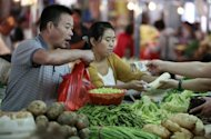 People buy vegetables at a market in Huaibei, China&#39;s Anhui province. China has already taken steps this year to stimulate growth by cutting interest rates twice in quick succession