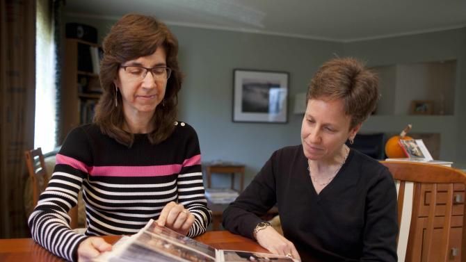 In this photo taken Monday, Nov. 12, 2012, Karen Golinski, left, and Amy Cunninghis, look over a photo album of their wedding photos in San Francisco. All Golinski wanted was to enroll her spouse in her employer-sponsored health plan. Four years later, her request still is being debated. Because Golinski is married to another woman and she works for the federal government, her personal personnel problem has morphed into a multi-pronged legal attack by gay rights activists to overturn the 1996 law that defines marriage as the union of a man and a woman. (AP Photo/Eric Risberg)