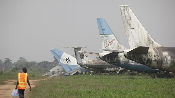 A man walks toward a row of abandoned airplanes at Murtala Muhammed International Airport in Lagos, Nigeria, Thursday, Jan. 31, 2013. Nigerian aviation officials have begun trying to dismantle and remove the hulks of abandoned aircrafts from airports around this nation with a history of aviation disasters. Officials say there are least 65 abandoned planes at the country's airports, with at least 13 at Lagos' international airport. (AP Photo/Sunday Alamba)