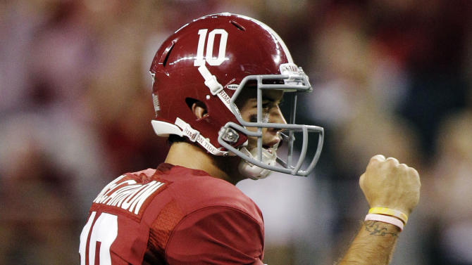 Alabama quarterback AJ McCarron (10) pumps his fist after a touchdown during the first half of an NCAA college football game against the Michigan at Cowboys Stadium in Arlington, Texas, Saturday, Sept. 1, 2012. (AP Photo/LM Otero)