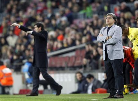 Barcelona's coach Martino looks at the pitch as Villarreal's coach Garcia gestures during their Spanish First division League soccer match at Camp Nou stadium in Barcelona