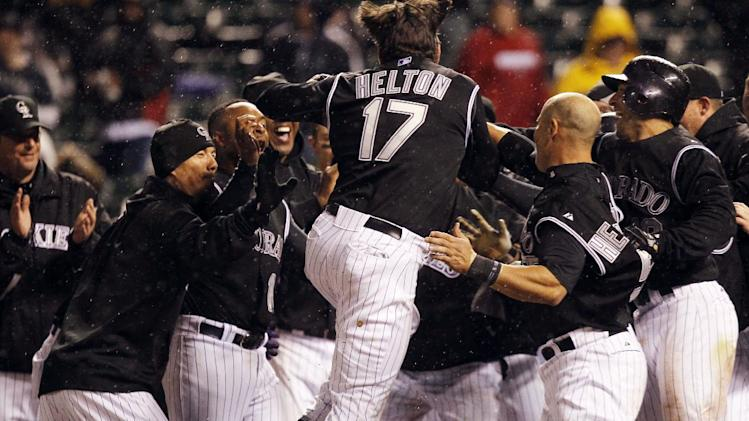 Colorado Rockies' Todd Helton, center, jumps into arms of his teammates as Helton crosses home plate after hiting a two-run, walkoff home run against the Arizona Diamondbacks in the ninth inning to give the Rockies' 8-7 victory in a baseball game in Denver on Saturday, April 14, 2012. (AP Photo/David Zalubowski)