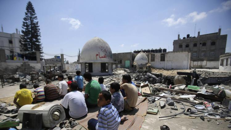 Palestinians perform Friday prayers among the ruins of a mosque in Rafah