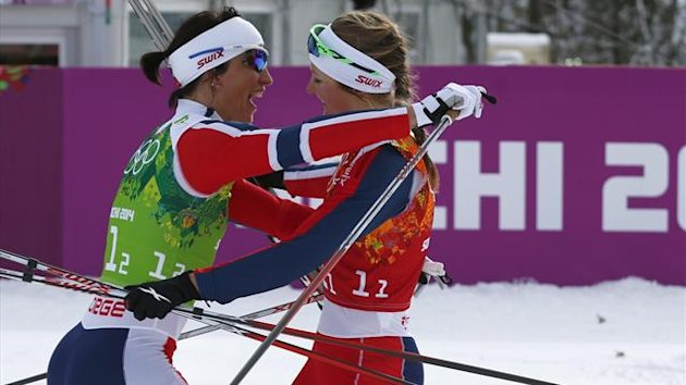 Norway's Marit Bjoergen and her team mate Ingvild Flugstad Oestberg (R) celebrate after crossing the finish line during the women's cross-country team sprint classic final at the Sochi 2014 Winter Olympics February 19, 2014. REUTERS/Michael Dalder (RUSSIA