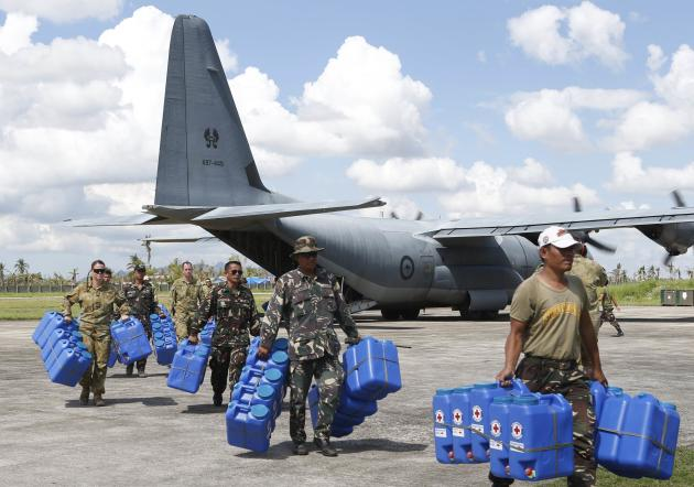 Australian and Filipino soldiers carry water containers for super Typhoon Haiyan survivors in Ormoc city in central Philippines
