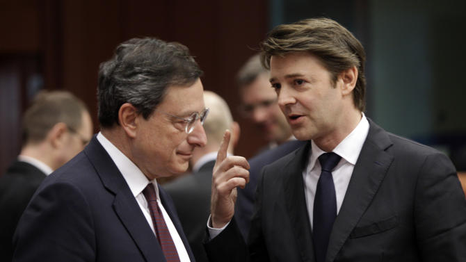 French Finance Minister Francois Baroin, right, speaks with European Central Bank President Mario Draghi during a meeting of EU finance ministers in Brussels on Monday, Jan. 23, 2012. European finance ministers will try on Monday to give new momentum to talks on a Greek debt relief deal that is crucial to avoid a default, but a European diplomat warned that a final agreement may have to wait until a leaders' summit next week. (AP Photo/Virginia Mayo)