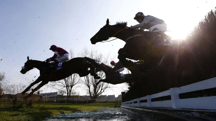 Horses and riders clear the water jump during the RSA Steeple Chase at the Cheltenham Festival horse racing meet in Gloucestershire