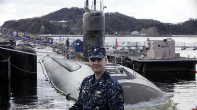 In this Monday, March 12, 2012 photo, Commander Ian Johnson stands in front of the USS Connecticut, a Sea Wolf-class nuclear submarine, during a port call at a U.S. naval base at Yokosuka, south of Tokyo, Japan. The submarine took part in exercises at the North Pole in 2011 to improve the U.S. Navy's operations in the Arctic. To the world's military leaders, the debate over climate change is long over. They are preparing for a new kind of Cold War in the Arctic, anticipating that rising temperatures there will open up a treasure trove of resources, long-dreamed-of sea lanes and a slew of potential conflicts. (AP Photo/Greg Baker)