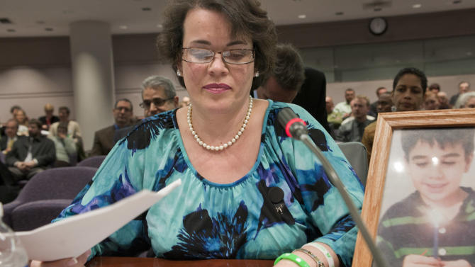 Veronique Pozner places her hand next to artwork made by her son Noah's  before testifying before a hearing of a legislative subcommittee reviewing gun laws at the Legislative Office Building in Hartford, Conn., Monday, Jan. 28, 2013.   Pozner, whose son Noah was killed in the Sandy Hook School shooting, told lawmakers about dropping off two of her daughters at the new Sandy Hook Elementary School in Monroe, and then visiting her son's grave, just five minutes away, to bring a teddy bear. (AP Photo/Jessica Hill)