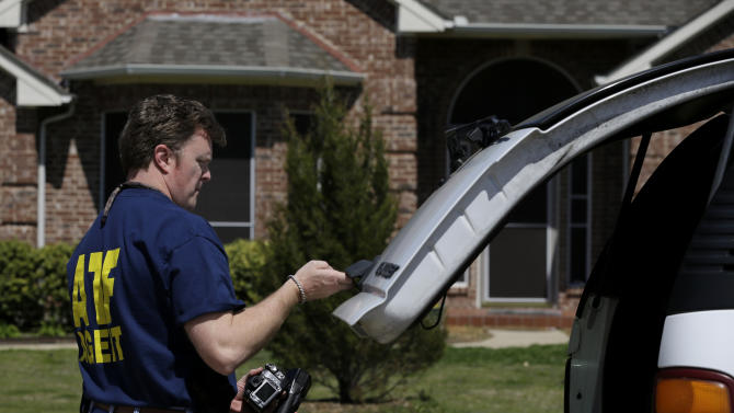 An ATF agent pulls some equipment from his vehicle as he prepares to go into the home of Kaufman District Attorney Mike McLelland Monday, April 1, 2013, near Forney, Texas. McLelland and his wife were both murdered at their home Saturday. (AP Photo/Tony Gutierrez)