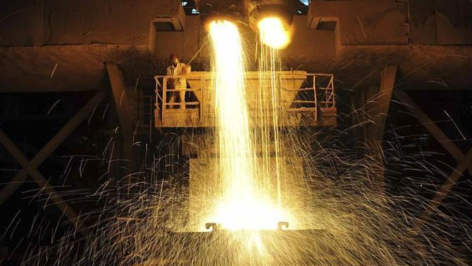 Labourer guides as slag is poured into a container at Dongbei Special Steel Group Co. Ltd. in Dalian