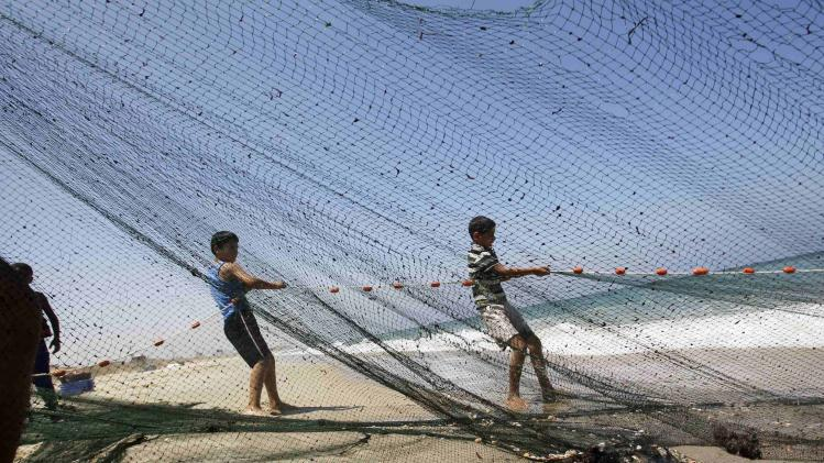 Palestinians pull a fishing net during the first few hours of a humanitarian ceasefire, on a beach in Gaza City