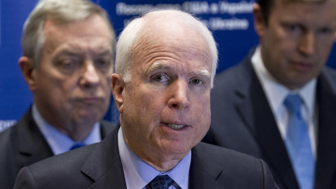 U.S. Sen. John McCain, R-Ariz., center, speaks during a news conference in Kiev, Ukraine, Saturday, March 15, 2014. McCain and a team of seven other senators concluded their visit in Kiev on Saturday with a news conference in which they reaffirmed their support to the interim Ukrainian government. (AP Photo/David Azia)