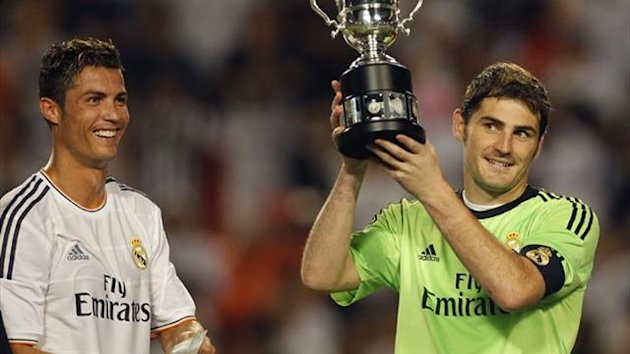 "Real Madrid's Iker Casillas (R) hoists the winning trophy next to teammate Cristiano Ronaldo, holding the ""Man of the Match"" trophy, after their victory over Chelsea (Reuters)"
