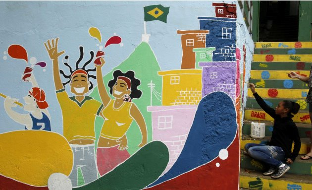 A girl paints graffiti on a wall at the at the Babilonia slum in Rio de Janeiro