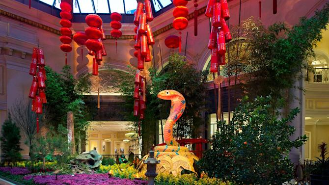 This January 2013 photo provided by MGM Resorts International shows the Chinese New Year floral display at the Bellagio Conservatory & Botanical Gardens in Las Vegas welcoming the year of the snake. The display includes a money tree decorated with gold coins, red lanterns, a 9-foot snake, a waterfall and wooden boat. It's one of a number of exhibits and events around Las Vegas marking the year of the snake, which begins on Feb. 10. (AP Photo/MGM Resorts International)
