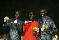 Kenyan silver medalist Abel Kirui (left) and Kenyan bronze medalist Wilson Kipsang Kiprotich (right) with Uganda's gold medalist Stephen Kiprotich (C) at the Olympic men's marathon medal ceremony. Kenya's Olympic performance has led to acrimonious debate at home, after the squad bagged only 11 medals
