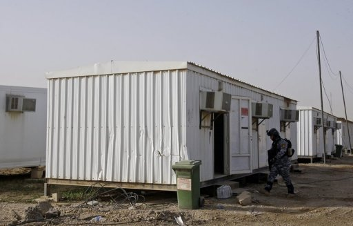 An Iraqi soldier inspects prefabricated houses in February 2012 at the former US military base Camp Liberty, which will be the new temporary home of exiled members of the People's Mujahedeen of Iran
