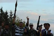 "Syrian rebel fighters brandish their weapons and flash the ""V"" for victory sign near a post in the rebel-held Syrian city of Minbej. The Syrian regime rejected a UN call for a unilateral ceasefire on Wednesday as rebels confronted columns of tanks and troops sent to retake a town on the road to main battleground city Aleppo"