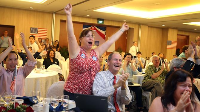 Obama supporters, Don and Mallory Riegger of Tucson, Arizona, center celebrate after hearing the news of U.S. presidential election results Wednesday, Nov. 7, 2012 in Singapore. Americans and supporters gathered at the American Club in Singapore to watch the live coverage of the election. (AP Photo/Wong Maye-E)