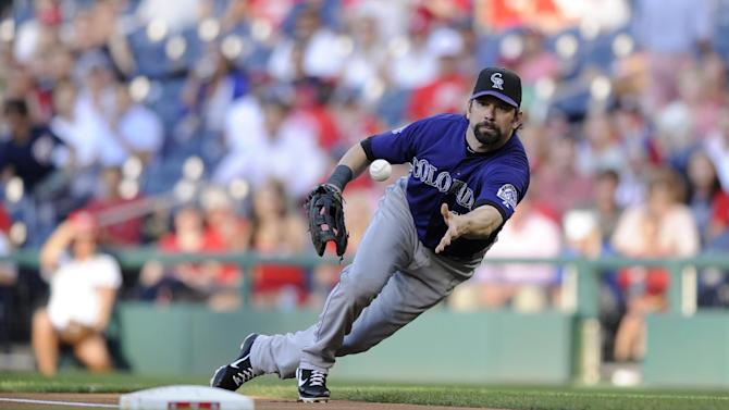 Colorado Rockies first baseman Todd Helton tosses the ball to Tyler Chatwood, not seen, to get out Washington Nationals' Denard Span out at first on a grounder during the first inning of a baseball game, Friday, June 21, 2013, in Washington. (AP Photo/Nick Wass)